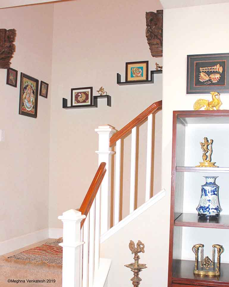 A stairway with yazhis and Tanjore paintings.