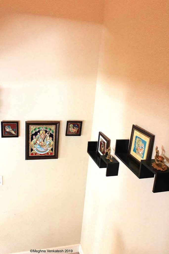 A Tanjore swan painting and lamp each on two floating shelves on one of the walls in the stairway.    The other wall has a Tanjore painting of Saraswathi with two smaller Tanjore swan paintings on either side. One of the lamps on the floating shelf is of Lord Brahma, whose consort is Saraswathi. Hence, the idea to place the Brahma lamp close to the Saraswathi Tanjore painting was to signify the connection between the two gods.