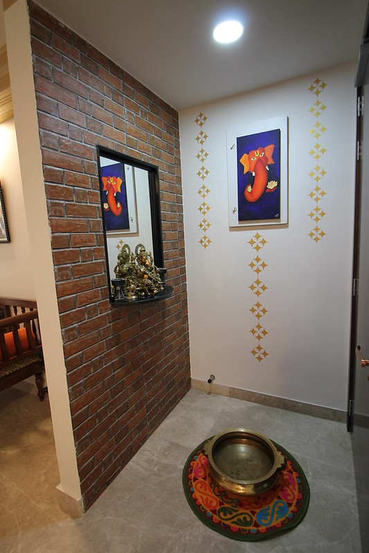 Exposed brick clad wall in the foyer with a brass uril and Ganesha