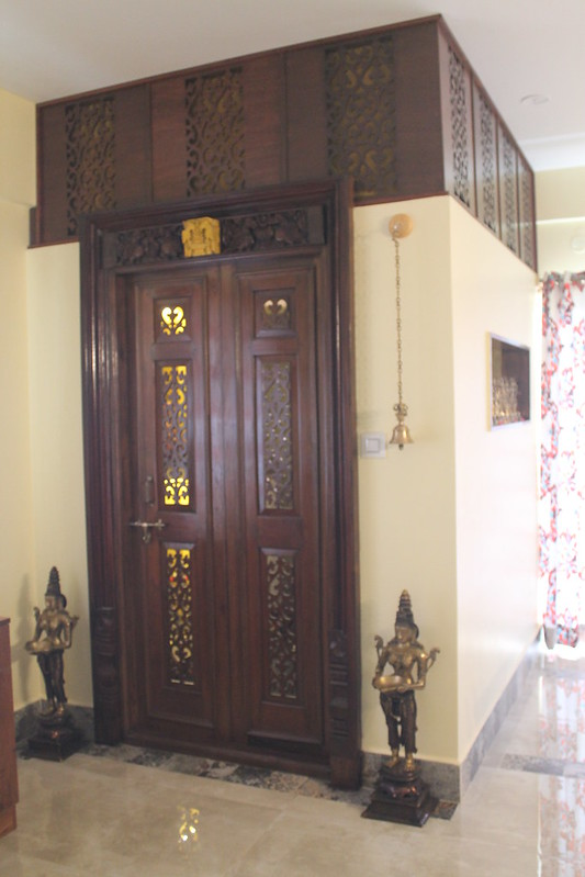 Intricately carved wooden pooja door design with hanging brass bells and wall niches for lighting lamps.