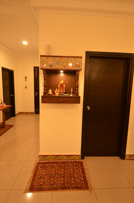A compact wall mounted mandir or pooja design in living room.