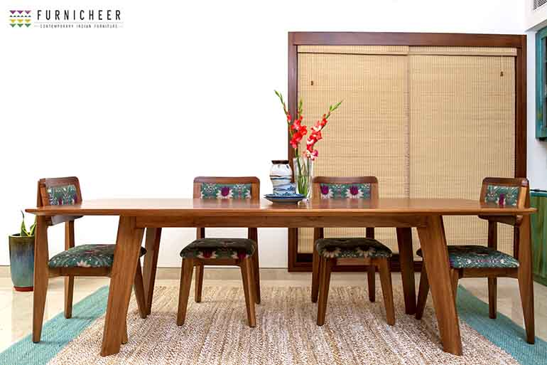 A custom made dining table with upholstered chairs adding to the rustic and earthy look of the space.