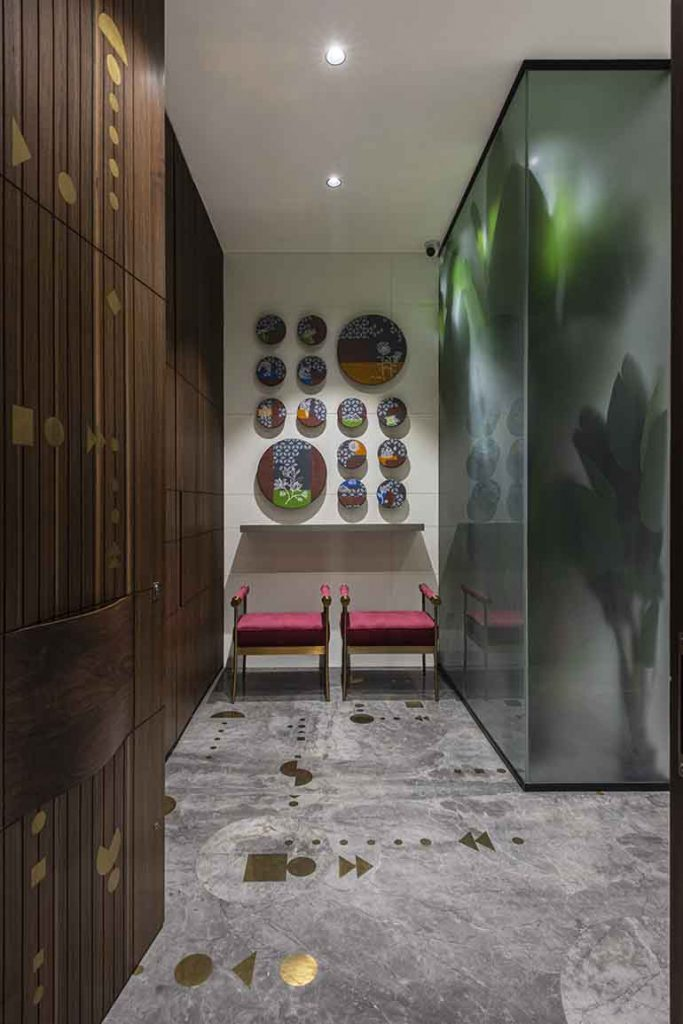 Foyer: the flooring has the same inlay pattern in brass  derived from Bandhani;, the circular plates represent the five elements of life - ????????? ????  are painted on MDF . This is the first thing that greets visitor. Design by Surat based architect Studio 17