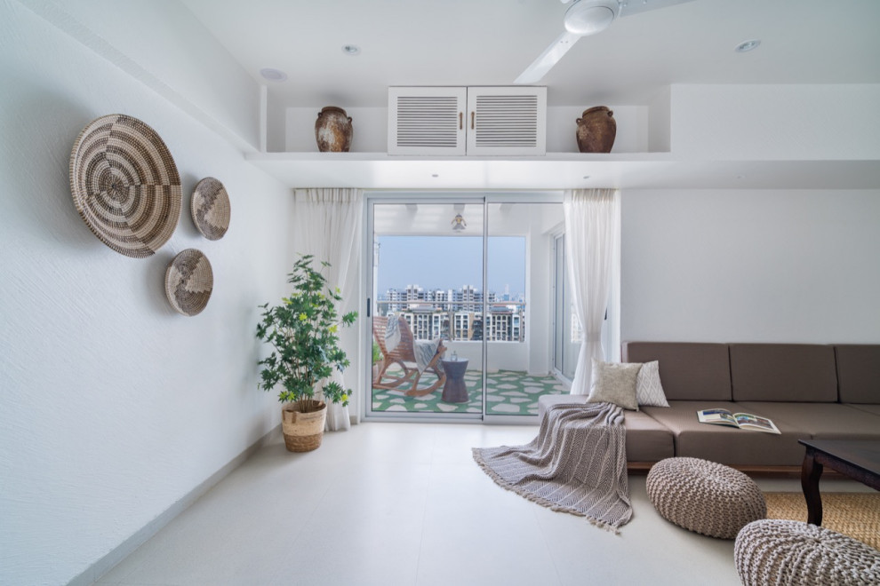 An all white living room that opens up into a balcony. Earthy palette of browns and creams is used for a recall factor of the sand at the seashore. Designed by Pune based interior design firm Between Walls.