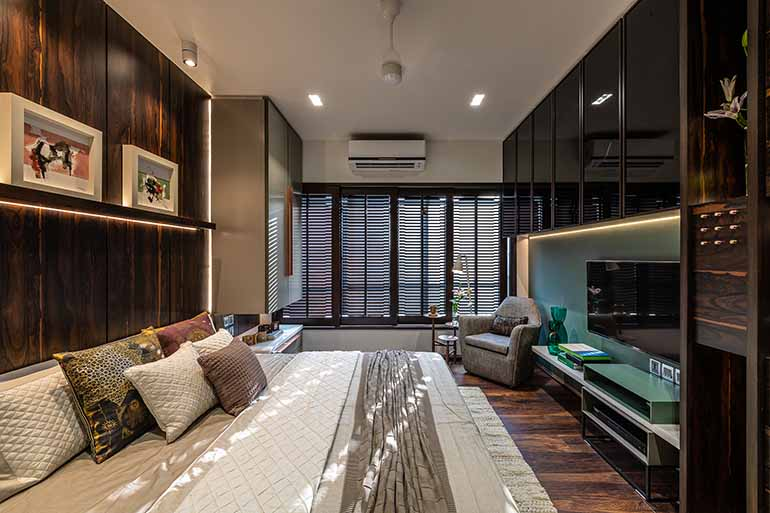 In a small space, dark tones work well to give the bedroom a snug and cosy look much against the perception of using light color to make it feel big. Louvered sliding shutters instead of curtains provide privacy for the master bedroom.