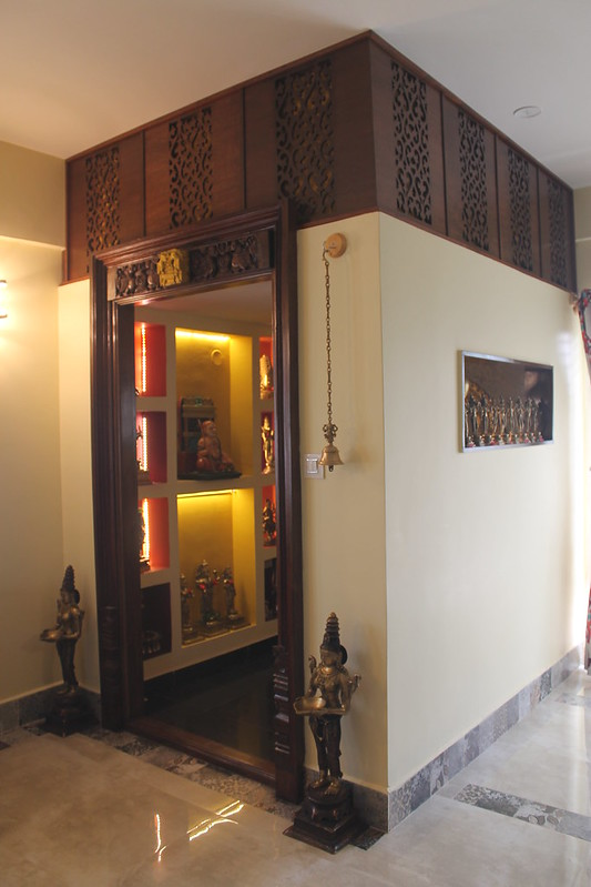 Intricately carved pooja door design with backlit wall niches. Modern inside, traditional outside.
