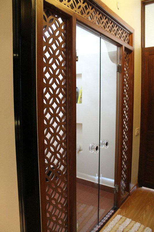 Pooja room design with glass doors and red oxide flooring.