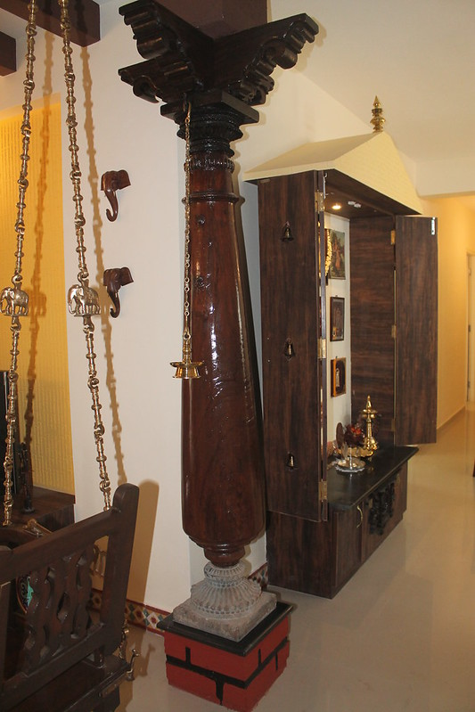 Wooden pillars flank this pooja room with foldable door design. It has a storage at the bottom and nails for hanging photos of deities.