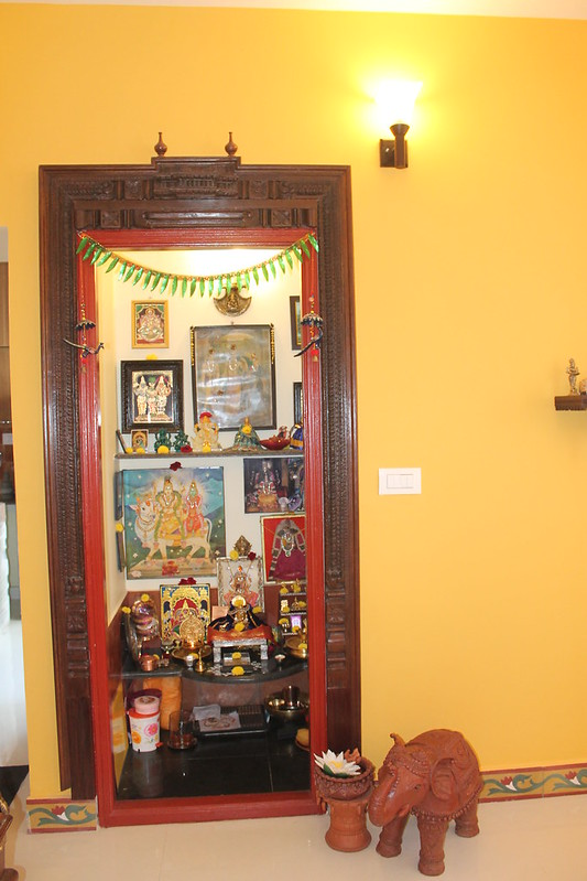 Traditional pooja room with wooden doors, granite slab