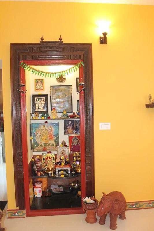 Traditional pooja room with wooden doors, granite slab