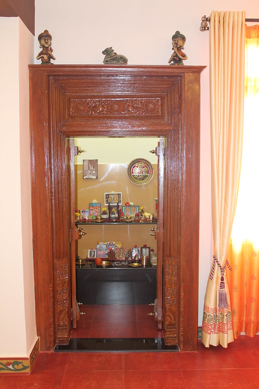 Traditional separate pooja room design with red oxide flooring and granite slab.