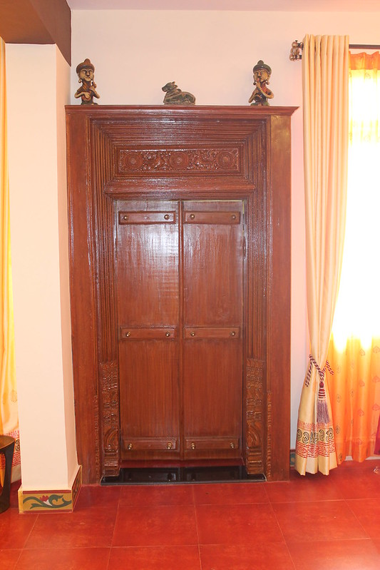 Traditional South Indian two door pooja room design with red oxide flooring.