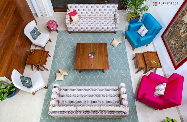 The furniture is upholstered in the client's chosen colors: turquoise and pink paving the way for a colorful living room. The three-seater sofas are draped in a more subdued, traditional bhutta patterned fabric, and the chairs in white Chanel fabric.