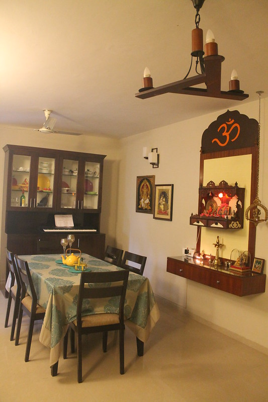 Wall mounted puja cabinet with drawers for storage and Tanjore painting on either side.