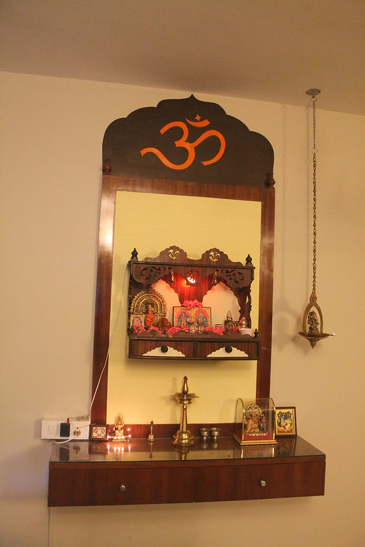 Compact wall mounted puja cabinet with hanging brass bells and drawers for storage.